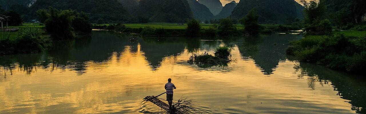 Mies soutaa lammessa auringonlaskiessa.