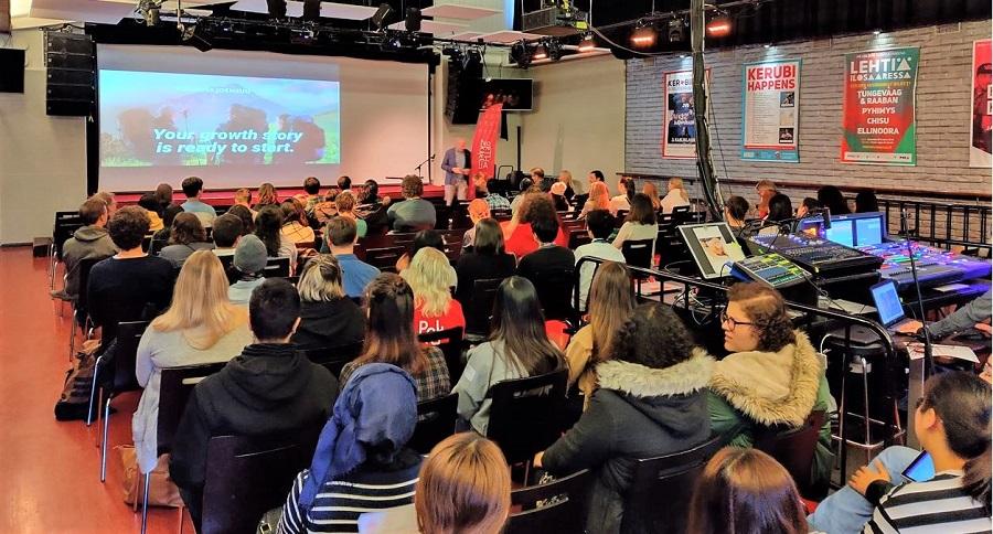 Kuvassa paljon opiskelijoita istumassa tuoleilla. He ovat katsomassa luentoa, joka esitetään PowerPoint muodossa.
