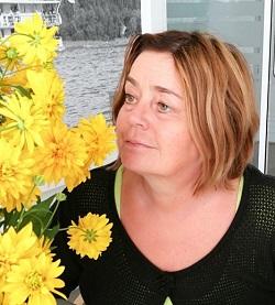 Kati Säisä poseeraa keltaisen kukan kanssa.