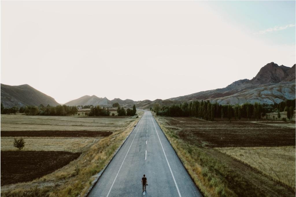 Vuoristomaisema, jonka läpi kulkee asfalttitie. Tien päässä mies kameran kanssa katsoo kaukaisuuteen.