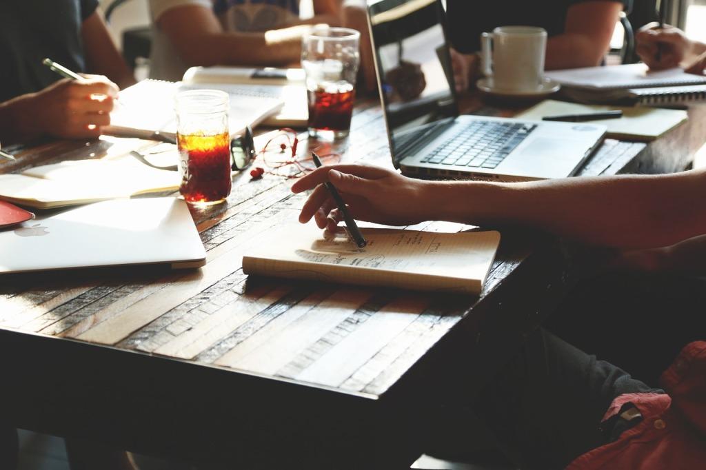 Pöydän ääressä ihmiset pitävät palaveria ja suunnittelevat yrityksen tulevaa. Pöydällä vihkojen lisäksi, tietokone sekä juomia.