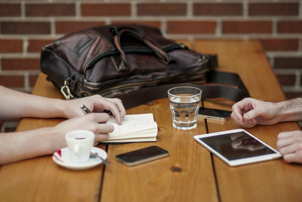 Pöytä, jossa näkyy neuvottelijoiden kädet. Pöydällä on tietokonelaukku, tabletti, pari älypuhelinta, kahvikuppi ja vesilasi.