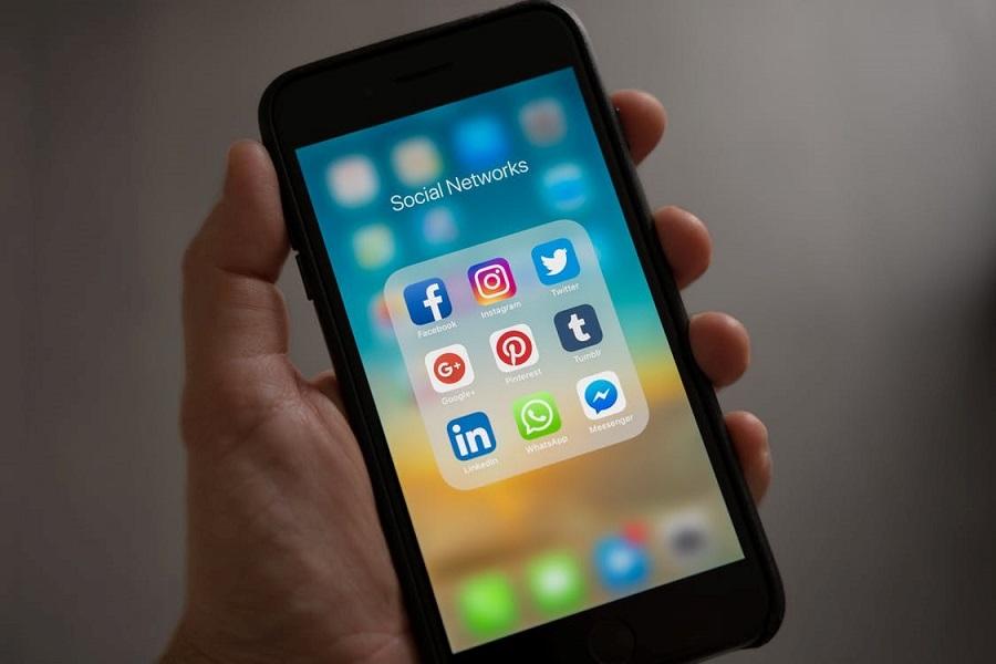 Kädessä äykännykkä, jonka näytöllä sosiaalisen median sovelluksia.