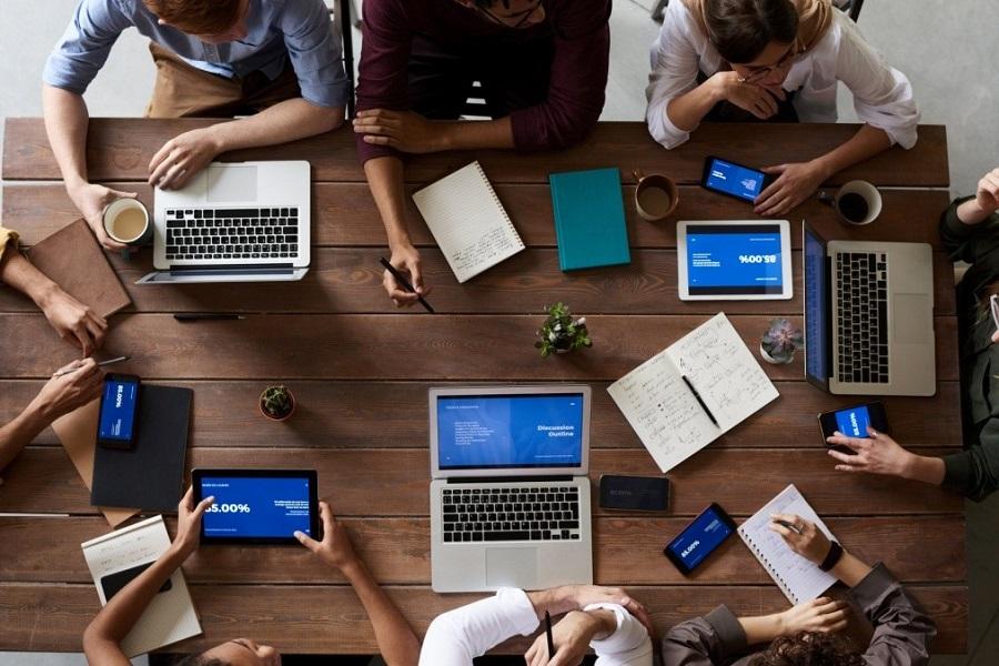 Pöydän ääressä ihmisä, jotka käyttävät kannettavia tietokoneita tai tabletteja.