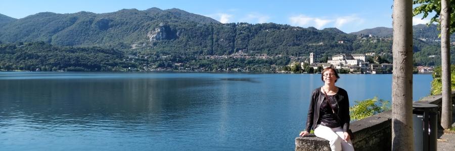 Outi Kaihola istuu kivetyksellä järvi taustalla.