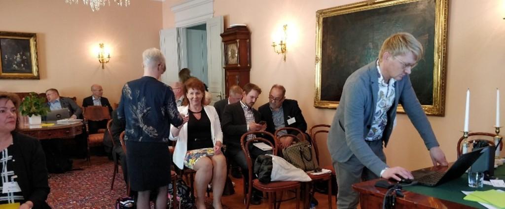 Ihmiset ovat odottamassa seminaarin alkamista, seminaarin juontaa Juuso Kalliokioski, joka on edessä laittamassa tietokonetta esityskuntoon.