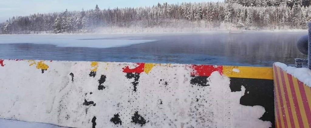 Kuva lossilta, takana talvinen järvi ja puut lumipeitteellä.