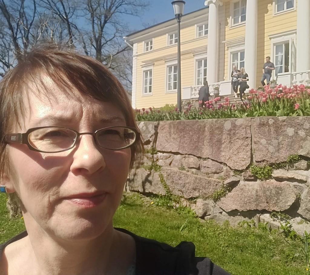 Outi  Kaihola kesäisessä ympäristössa, takana keltainen koristeellinen rakennus.