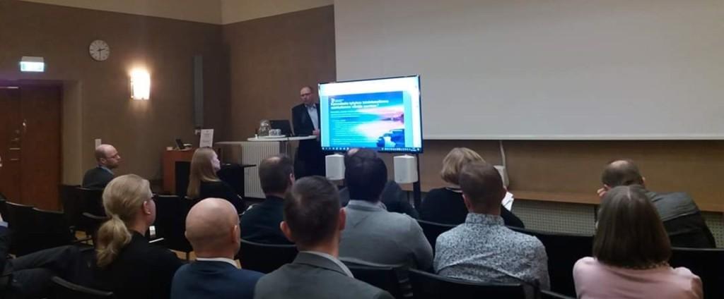 Ihmiset istuvat seminaarissa kuuntelemassa puhujaa Kalevi Pölönen.