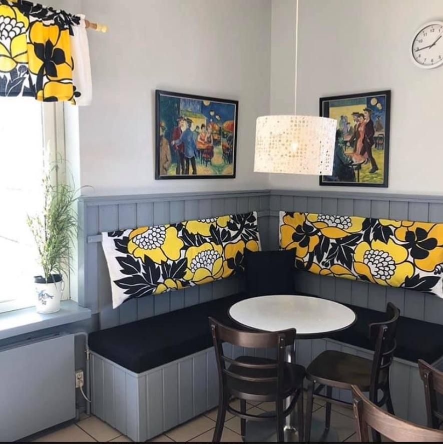 Kahvilassa penkit ja keltaiset istuintyynyt.