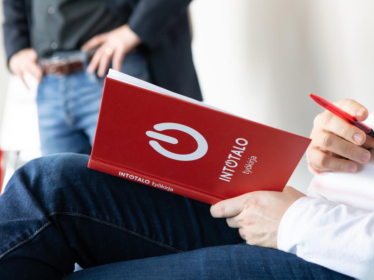 Henkilö pitää kädessään kirjaa.