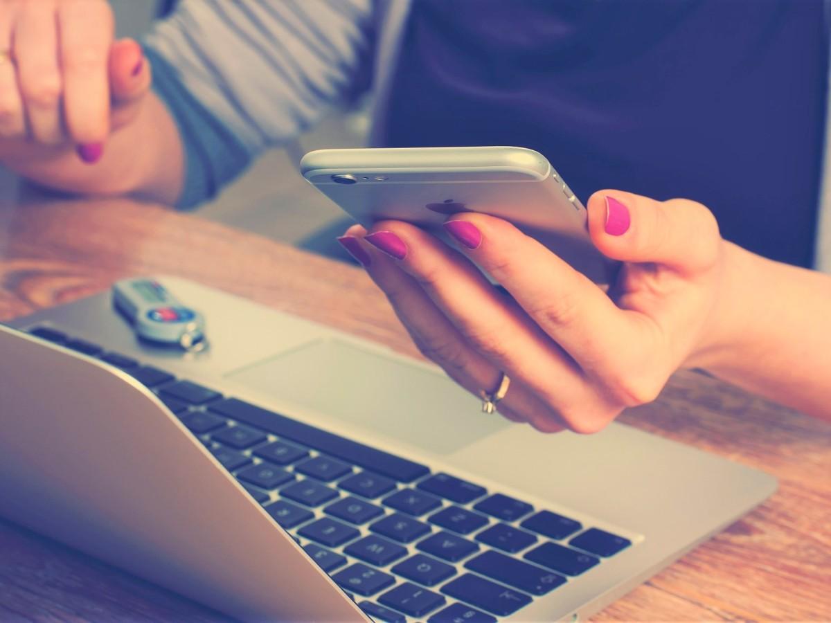 Nainen katsoo puhelinta tietokoneen äärellä.