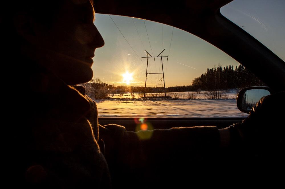 Mies ajaa autolla talvella auringonlaskun aikaan.