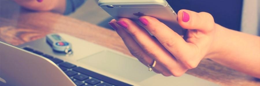 Naisen kädet kannettavan tietokoneen edessä puhelin kädessä.